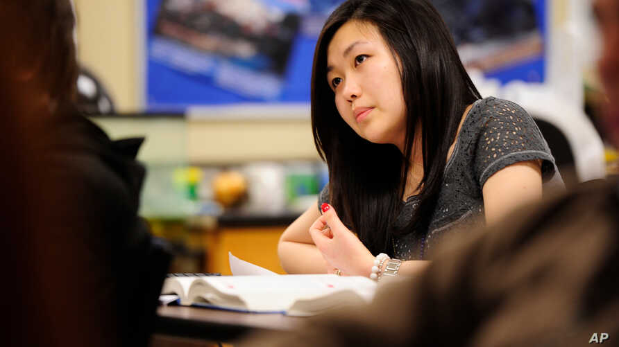 In this Feb. 27, 2012, photo, Sally Kim takes notes during a physics class at Columbia Independent School in Columbia, Mo. Kim…
