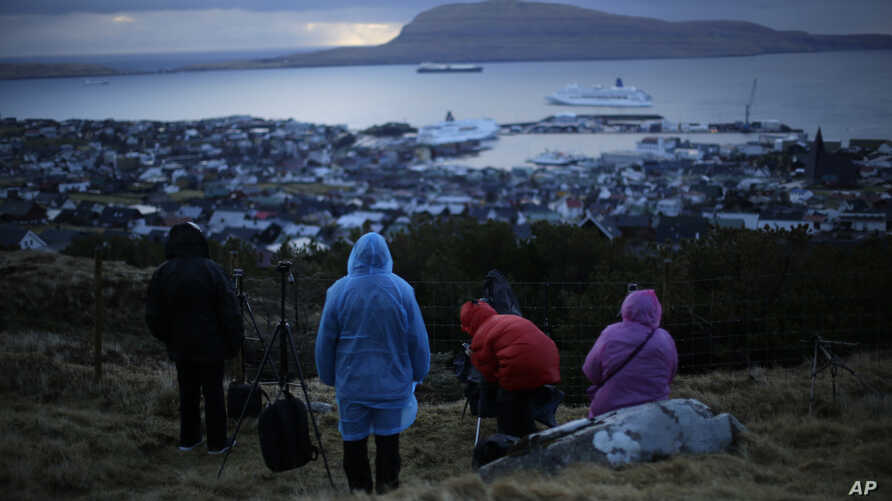 People wait for the start of a total solar eclipse on a hill beside a hotel overlooking the sea and Torshavn, the capital city…