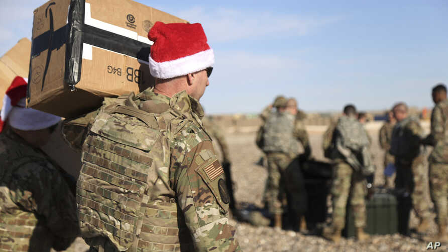 In this Monday, Dec. 23, 2019, photo, a U.S. soldier carries Christmas gifts from a helicopter to deliver to his comrades on a…