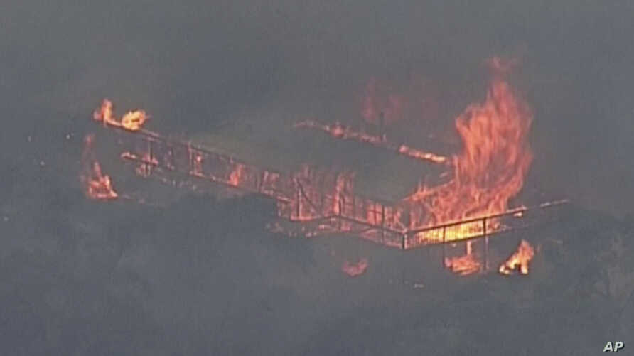 This image made from video shows a house on fire from a bushfire, Monday, Dec. 23, 2019, in Gumeracha, South Australia…