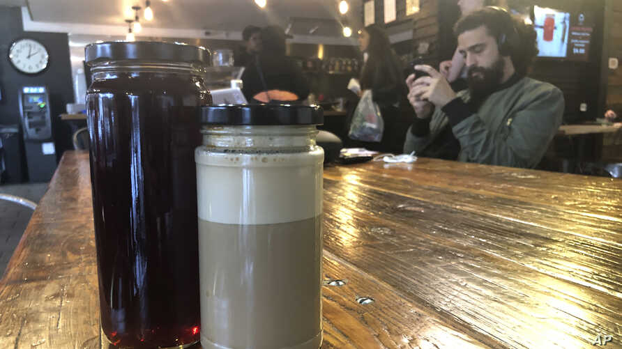 In this Thursday, Dec. 12, 2019 photo, reusable to-go glass jars rest on a counter top at the Perch Coffee Shop, which stopped…