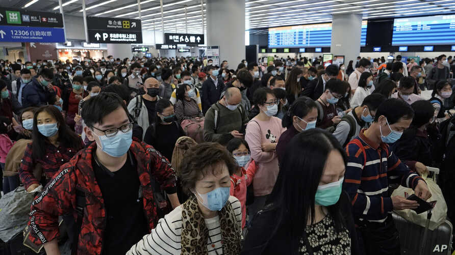 Passengers wear protective face masks at the departure hall of the high speed train station in Hong Kong, Thursday, Jan. 23,…