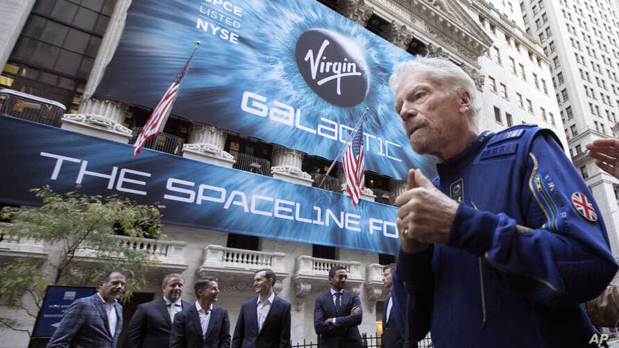 Sir Richard Branson, right, founder of Virgin Galactic, and company executives gather for photos outside the New York Stock…