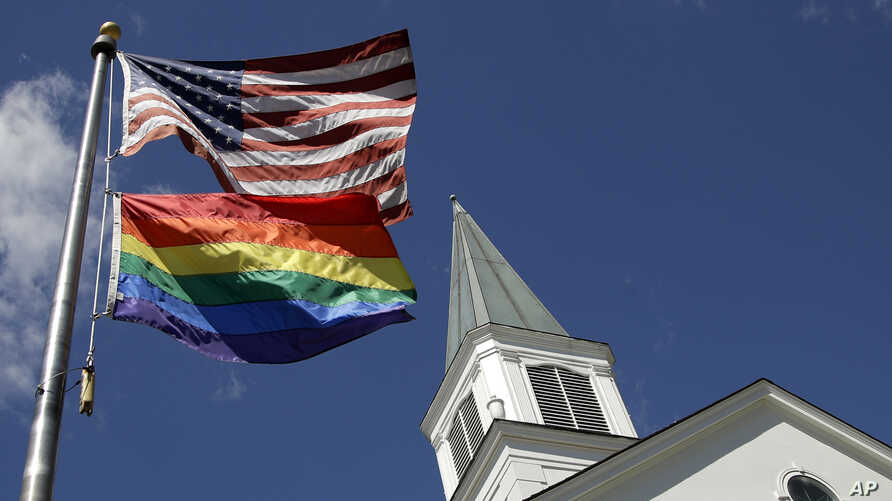 FILE - In this April 19, 2019, file photo, a gay pride rainbow flag flies along with the U.S. flag in front of the Asbury…