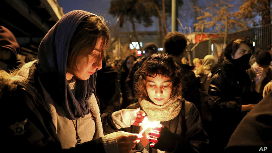 People gather for a candlelight vigil to remember the victims of the Ukraine plane crash, at the gate of Amri Kabir University…
