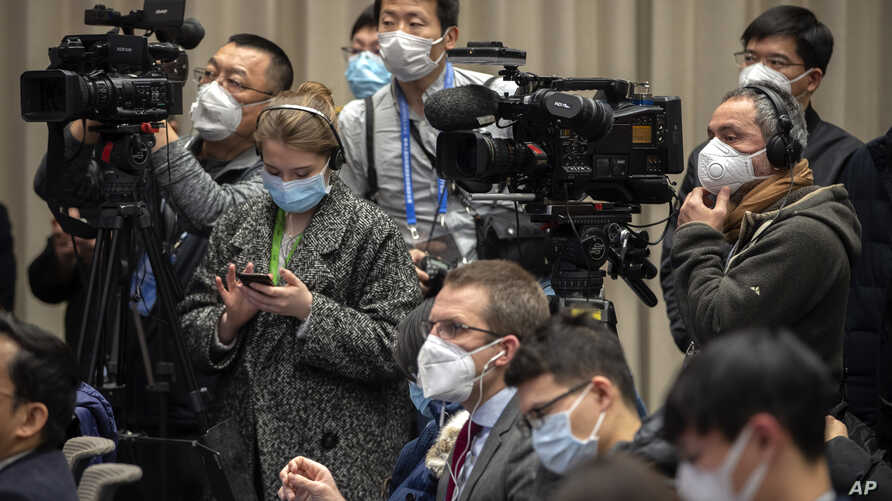 Journalists wearing face masks attend an official press conference about a virus outbreak at the State Council Information…