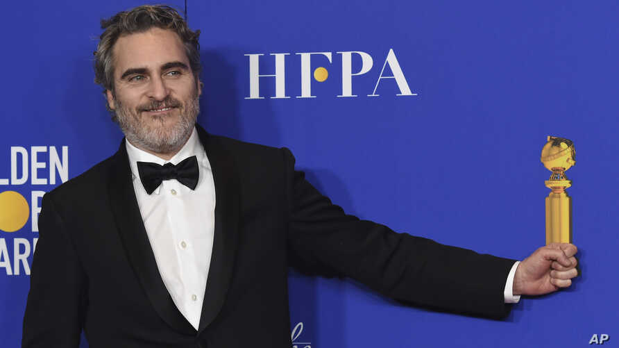"""Joaquin Phoenix pretends to hold his award for best performance by an actor in a motion picture drama for """"Joker"""" in the press…"""