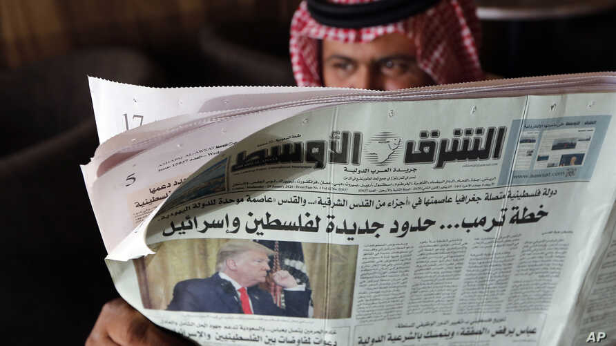 A man holds the daily Asharq Al-Awsat newspaper fronted by a picture of President Donald Trump, at a coffee shop in Jiddah,…