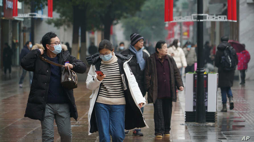 Masked pedestrians walk down a shopping street in downtown Wuhan, China, Wednesday,  Jan. 22, 2020. The number of cases of a…