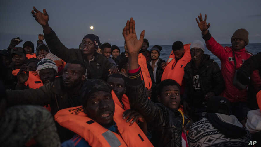 Migrants and refugees from different African nationalities sailing adrift on an overcrowded rubber boat, receive life jackets…