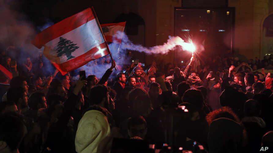 Anti-government demonstrators hold flares and Lebanese flags, during a protest on a road leading to the parliament building in…