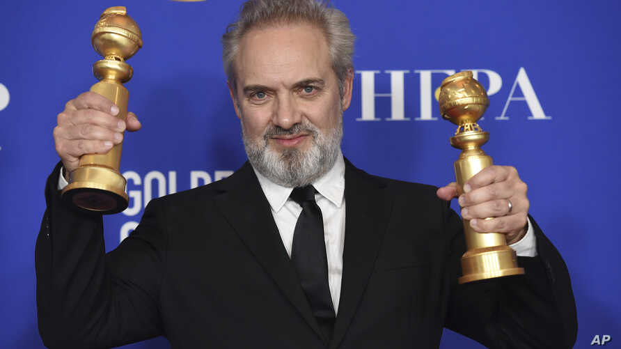 "Sam Mendes poses in the press room with the awards for best director, motion picture and best motion picture drama for ""1917""…"