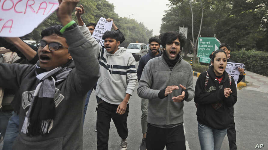 Students shout slogans as they march towards Uttar Pradesh Bhawan during a protest against a new citizenship law and violence…