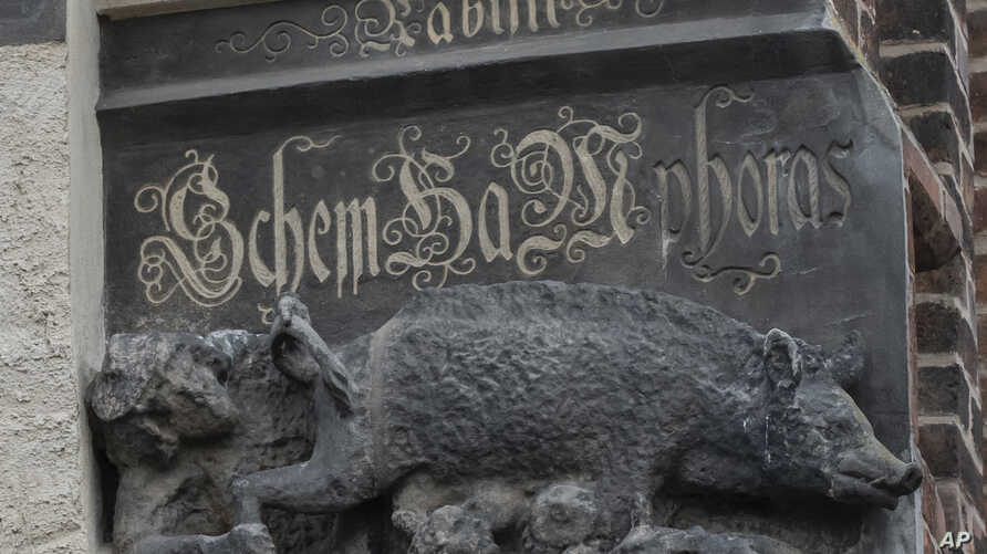 "In this Tuesday, Jan. 14, 2020 photo the so-called ""Judensau,"" or ""Jew pig,"" sculpture is displayed on the facade of the…"