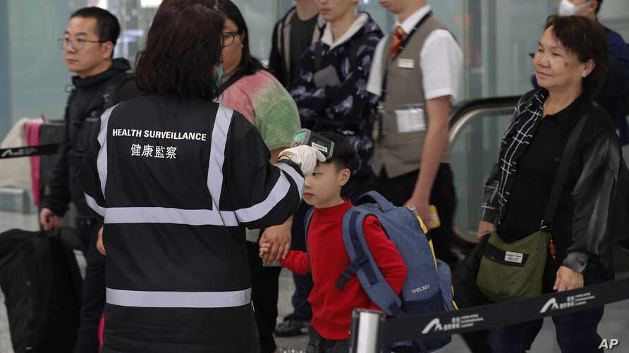 A health surveillance officer uses a device to check temperature of passengers near the immigration counters at the Hong Kong…