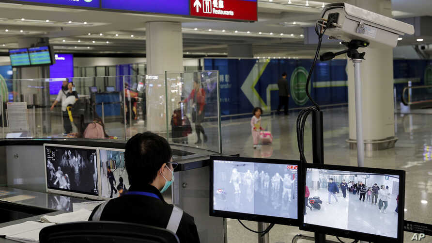 FILE - In this Jan. 4, 2020, file photo, a health surveillance officer monitors passengers arriving at the Hong Kong…