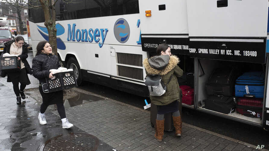 In this Dec. 30, 2019, photo, Jewish girls walk to a bus in the Crown Heights neighborhood of New York, for the trip to Monsey,…