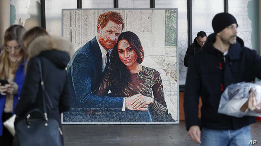 People walk past a picture of Britain's Prince Harry and Meghan Duchess of Sussex, in Windsor, Friday, Jan. 10, 2020. Britain's…