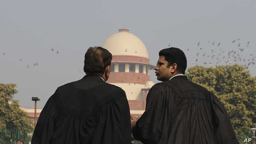Supreme Court Lawyers speak to each other on the lawns of India's Supreme Court as it begins hearing dozens of petitions that…