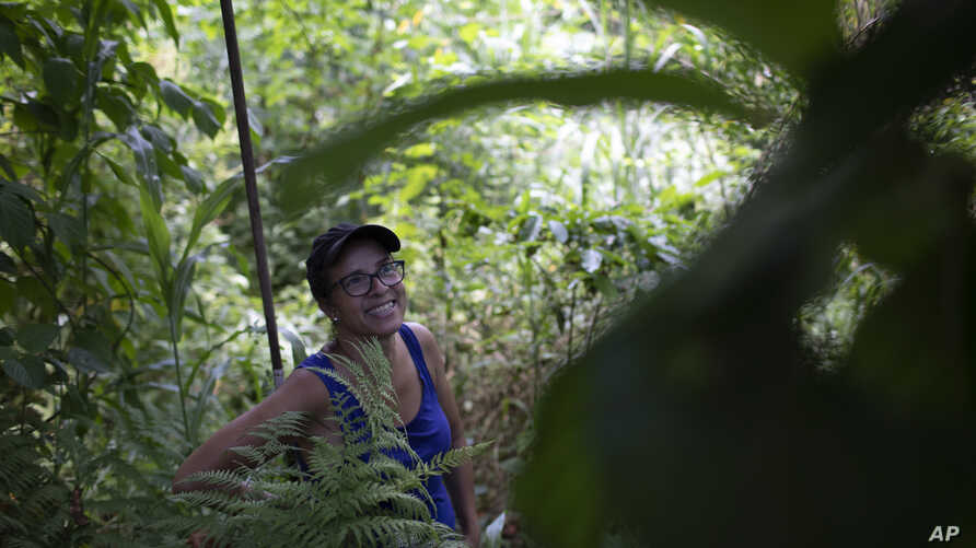 In this Jan. 6, 2020 photo, activist Ale Roque smiles as she sees a tree bearing fruit at her home in Rio's first favela, Morro…