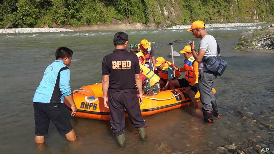 In this photo released by the Disaster Mitigation Agency of Bengkulu Province's Kaur District, rescue team prepares to search…