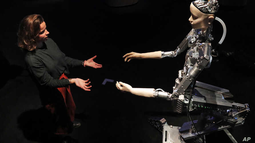 A woman interacts with a robot at the Barbican exhibition centre in London, Wednesday, May 15, 2019. Robots interact with…