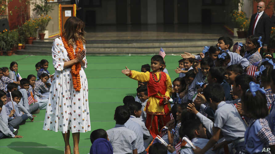 U.S. first lady Melania Trump greets Indian style as children try to reach out to shake hands with her at Sarvodaya Co…