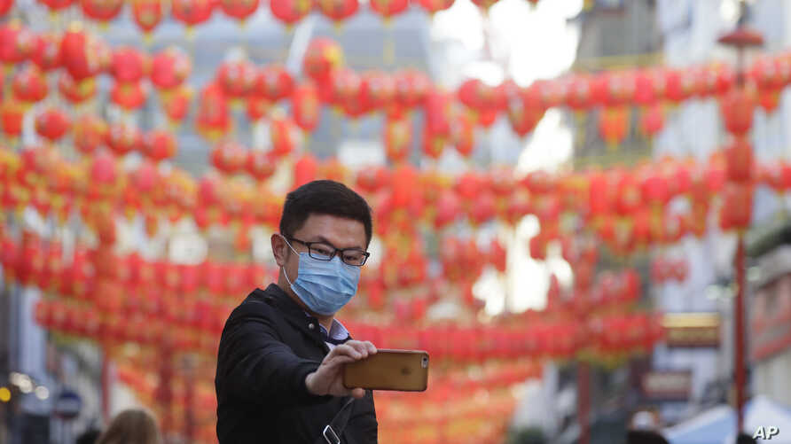 A man wears a mask as he takes a photograph in China Town in London, Friday, Feb. 7, 2020. The director-general of the World…