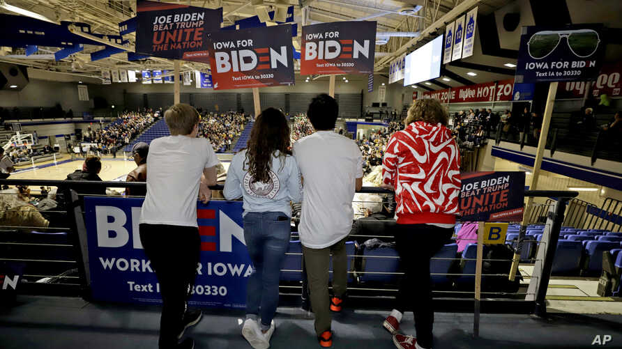 Younger caucus goers hold signs for Democratic presidential candidate former Vice President Joe Biden at the Knapp Center on…