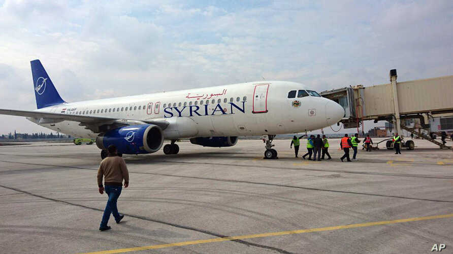 This photo released by the Syrian official news agency SANA, shows a Syrian commercial plane carrying Syrian officials and…