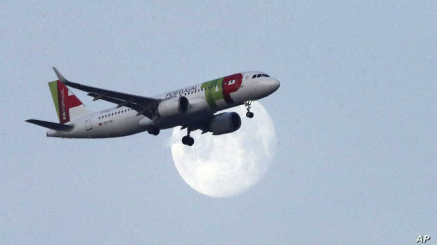 A TAP Air Portugal airplane approaches for landing in Lisbon as the moon sets, Thursday, Feb. 21, 2019. (AP Photo/Armando…