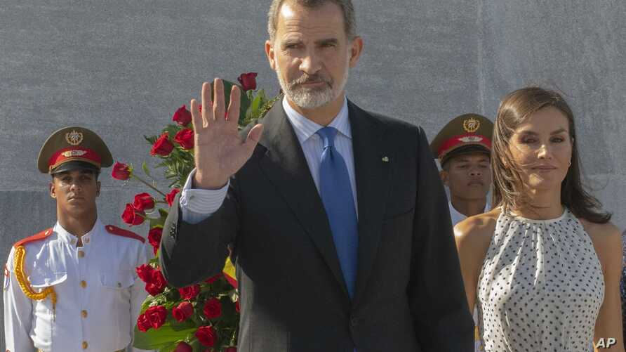 Spain's King Felipe VI waves as Queen Letizia walks with him after leaving a floral arrangement at the memorial for Cuban…