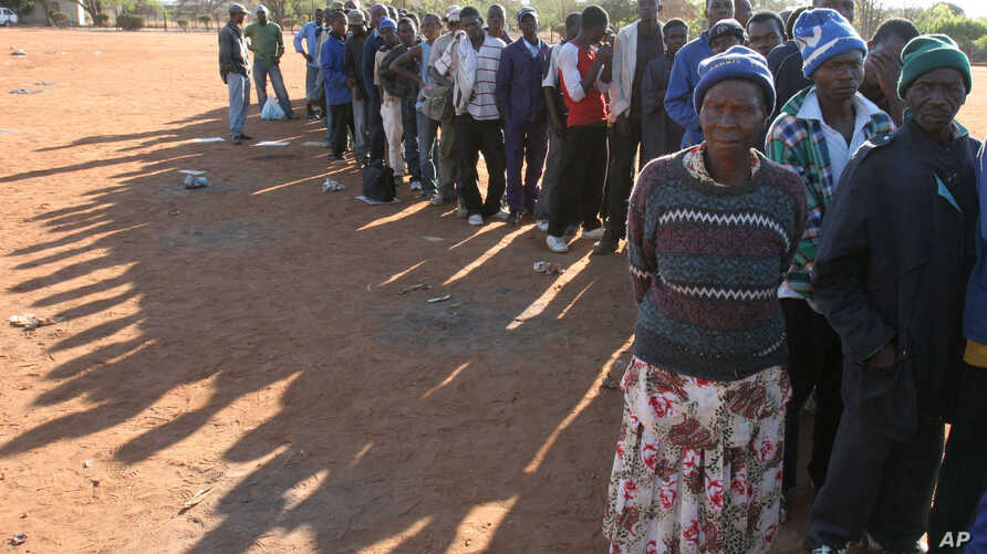 FILE - In this Sept. 16, 2008 file photo, Zimbabweans queue at Home Affairs offices in Musina, South Africa, close to the…