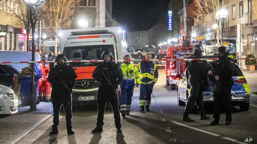 Police guard the scenery in front of a restaurant in central Hanau, Germany Thursday, Feb. 20, 2020. German police say several…