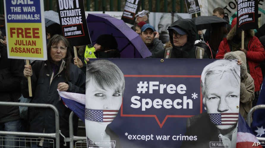 Supporters hold placards and banners during a protest against the extradition of Wikileaks founder Julian Assange outside…