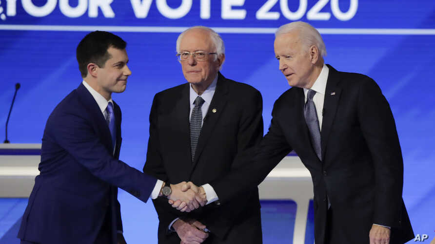 From left, Democratic presidential candidates former South Bend Mayor Pete Buttigieg, shakes hands with former Vice President…
