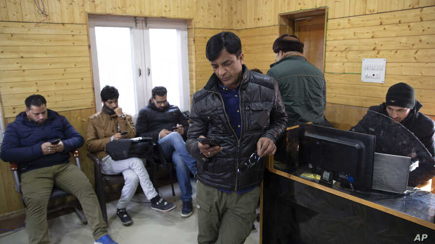 In this Jan. 30, 2020, photo, Kashmiri journalists browse the internet on their mobile phones inside the media center set up by…