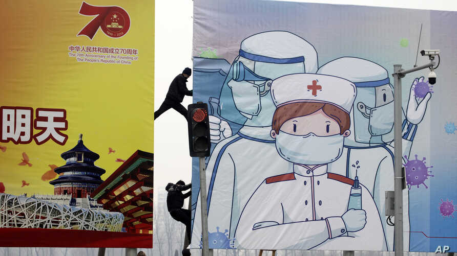 Workers put up government propaganda to fight against the viral outbreak in Beijing, China on Thursday, Feb. 20, 2020. A viral…
