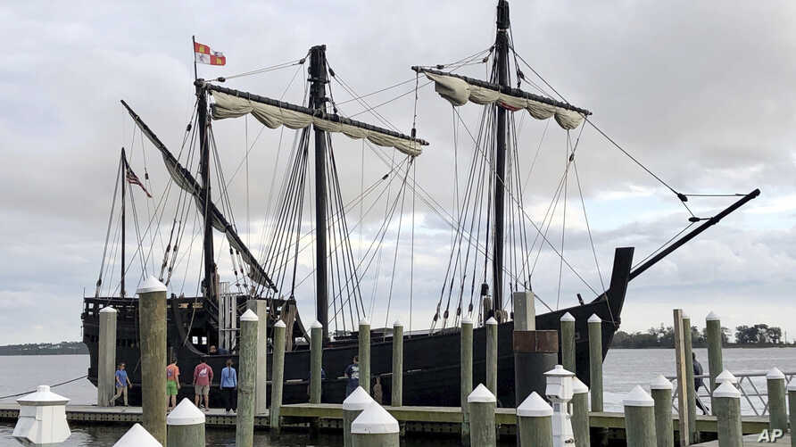 Spectators watch as a replica of one of Christopher Columbus' ships, the Pinta, is moored, Wednesday, Feb. 19, 2020, in Biloxi,…