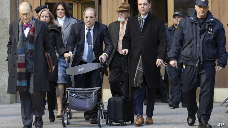 Harvey Weinstein, fourth from left, leaves the courthouse during jury deliberations in his rape trial, Friday, Feb. 21, 2020,…