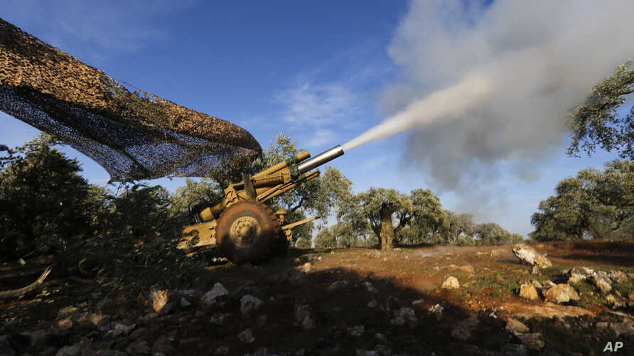 Turkish backed rebel fighters fire a howitzer toward Syrian government's forces positions near the village of Neirab in Idlib…