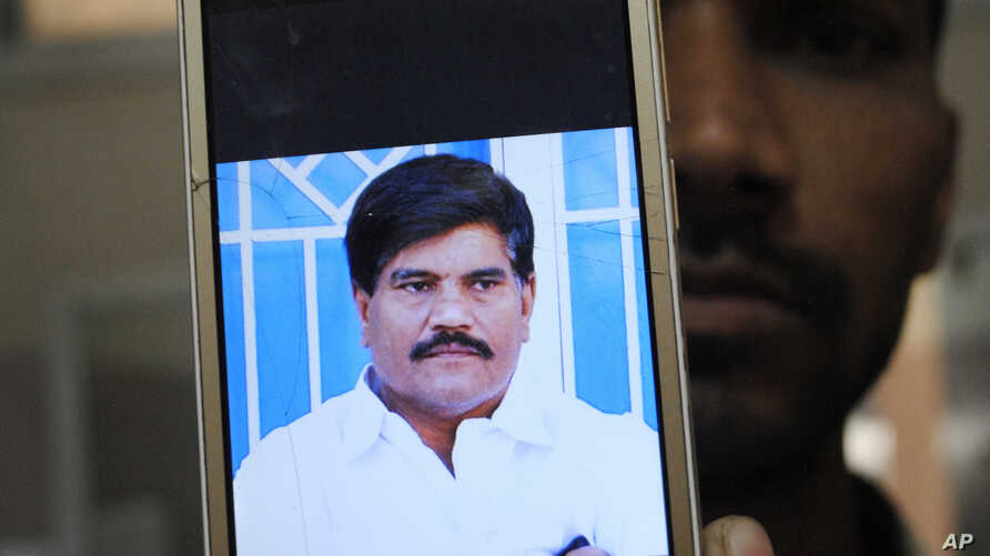 An employee of a local television channel shows a picture of slain journalist Aziz Memon on his mobile, after a demonstration…