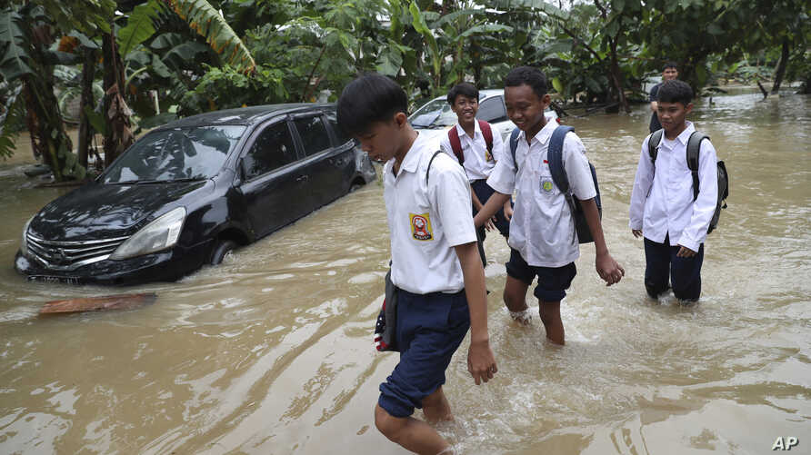 Students wade through a flood at a flooded neighborhood in Jakarta, Indonesia, Tuesday, Feb. 25, 2020. Overnight rains caused…
