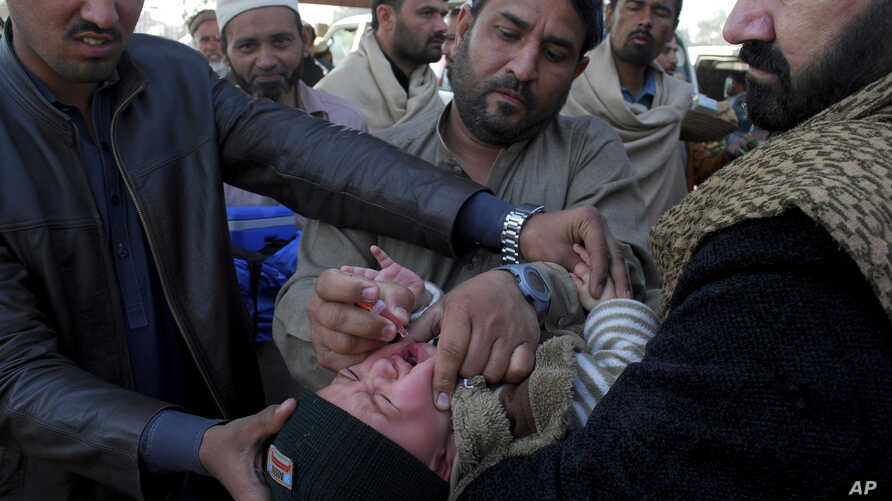 A health worker gives a polio vaccine to an Afghan refugee child in Peshawar, Pakistan, Tuesday, Feb. 18, 2020. Pakistan…