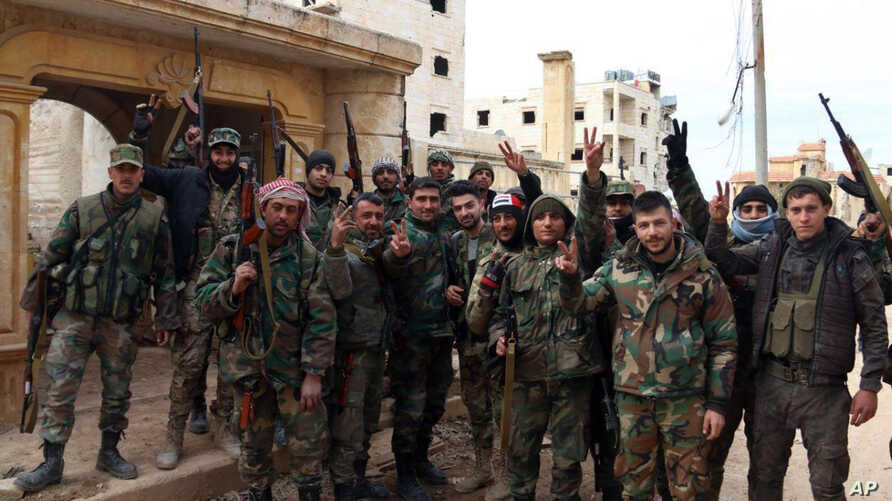 In this photo released Sunday, Feb. 16, 2020 by the Syrian official news agency SANA, Syrian army soldiers flash the victory…