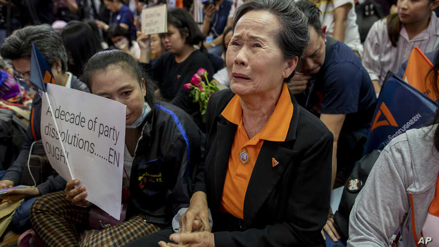 A supporter of Thailand's Future Forward Party cries as they watch a live television broadcast of a court verdict at their…
