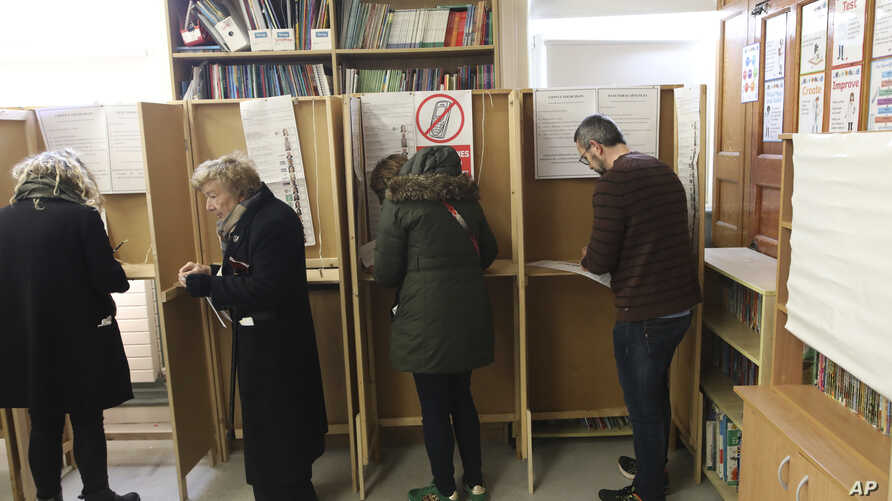 Voters make their decision at a polling station in North Dublin as voting gets under way in the general election in Dublin,…