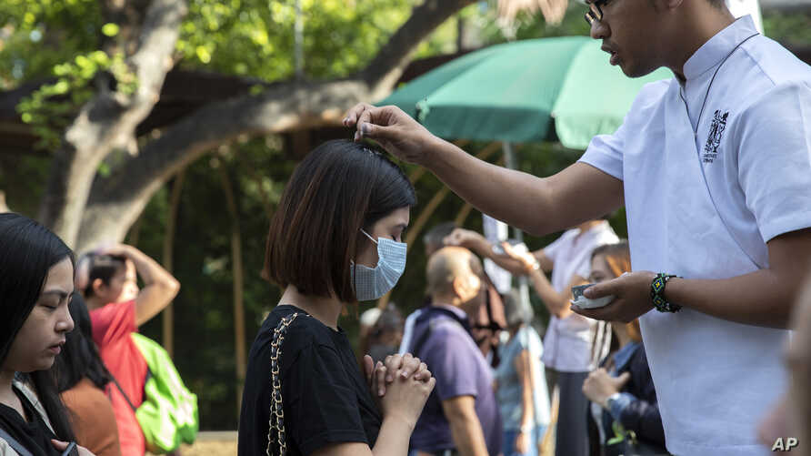 Catholic devotees have ash sprinkled on their heads during Ash Wednesday rites Feb. 26, 2020 in Paranaque, metropolitan Manila,…
