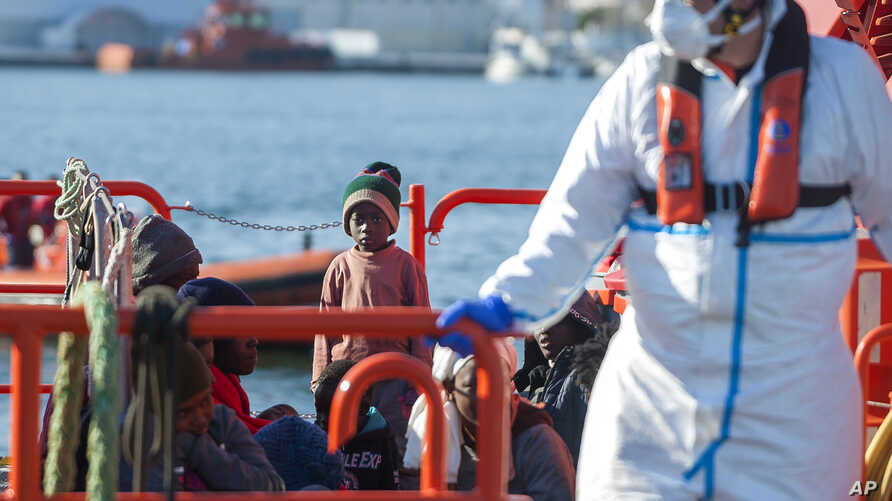 A child stands on a rescue vessel as he arrives with a group of migrants rescued by Spanish maritime authorities at Motril port…