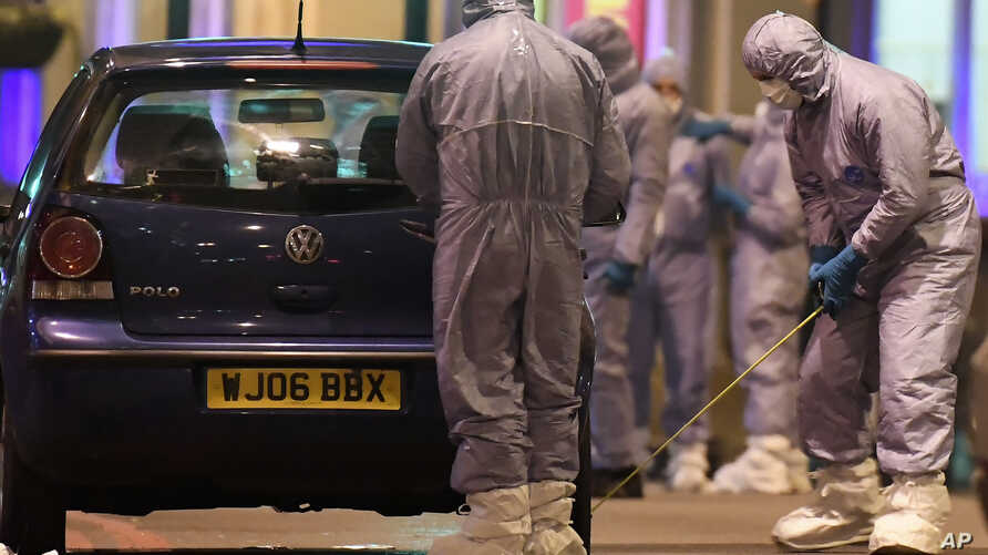 Police forensic officers work near a car at the scene after a stabbing incident in Streatham London, England, Sunday, Feb. 2,…